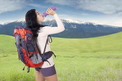 Woman with backpack drinks water at hill Royalty Free Stock Photography