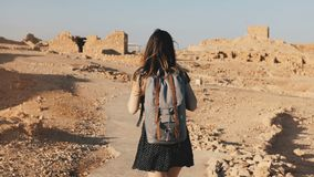 Woman with backpack explores ancient desert ruins. Beautiful European tourist walks on rocks and sand. Masada Israel 4K. Woman with backpack explores ancient stock footage