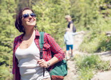 Woman with backpack in forest at the sunny day Royalty Free Stock Image