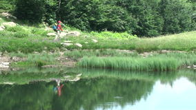 Woman with backpack hiker walking along the lake in the mountains. girl reflected in the lake stock video footage