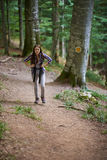 Woman with backpack hiking into the forest Royalty Free Stock Photos