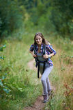 Woman with backpack hiking into the forest Stock Image
