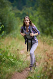 Woman with backpack hiking into the forest Stock Images
