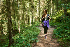Woman with backpack hiking into the forest Royalty Free Stock Image