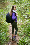Woman with backpack hiking into the forest Royalty Free Stock Photo