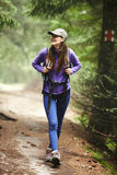 Woman with backpack hiking into the forest Royalty Free Stock Photography