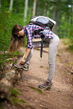 Woman with backpack hiking into the forest Stock Photo