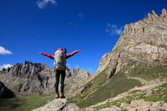 Woman with backpack hiking in mountains travel lifestyle success concept. Cheering woman with backpack hiking in mountains travel lifestyle success concept royalty free stock photography