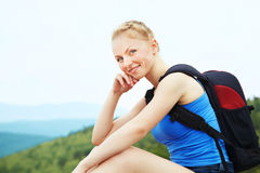 Woman with backpack hiking in the mountains Stock Photos