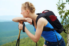 Woman with backpack hiking in the mountains Stock Images