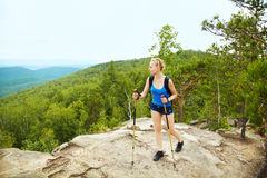 Woman with backpack hiking in the mountains Stock Photography