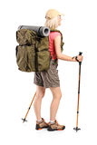 Woman with backpack and hiking poles posing Royalty Free Stock Images