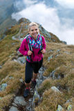 Woman with backpack hiking on a trail Stock Photo