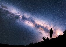 Woman with backpack on the hill against colorful Milky Way royalty free stock images