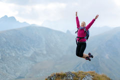 Woman jumping for joy on mountain top Stock Photo