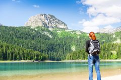 Woman with backpack on the lake Royalty Free Stock Photos