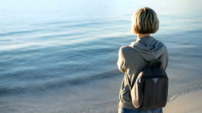 Woman with backpack looking at sea stock video footage