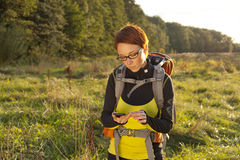 Woman with backpack looking to compass and searching the way / g Royalty Free Stock Photo