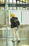 Woman with backpack looking train timetables Royalty Free Stock Photography