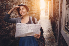 Woman with backpack and map in old town at sunset Stock Image