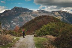 A woman with a backpack on the mountain route of Vermac in Montenegro with the visible massif of Lovcen. A woman on a mountain trail, the ridge of Vrmac, in the Stock Image