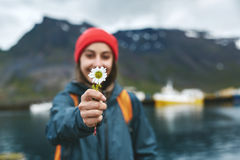 Woman with backpack on pier with flower. Back view of girl in warm clothing with backpack on pier with background of mountains of West Fjords, Iceland. woman Stock Photo