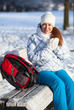 Woman with backpack rests on a bench in winter park Royalty Free Stock Photo