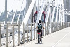 Woman with a backpack rides a bicycle on a bike path at Tilikum Crossing Bridge