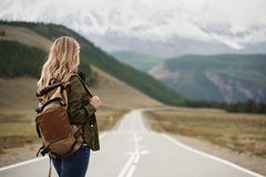 A woman with a backpack and a road stretching into the distance. Against the backdrop of mountains stock photo