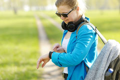 Woman with backpack on the shoulders uses of smart watches. Royalty Free Stock Images