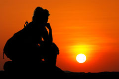 Woman with backpack sit on rock and looking at sunset Royalty Free Stock Photos