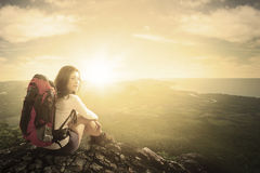 Woman with backpack sitting on mountain Royalty Free Stock Photography