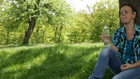 Woman with backpack sitting under the tree drinking water. Woman with backpack sitting under the tree enjoying shade and drinking water in a clearing of the stock footage
