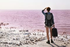 Woman with backpack and sleeping bag on coast. Of pink lake royalty free stock images