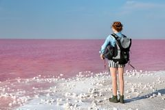 Woman with backpack and sleeping bag on coast. Of pink lake royalty free stock image