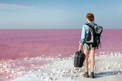 Woman with backpack and sleeping bag on coast. Of pink lake stock photography
