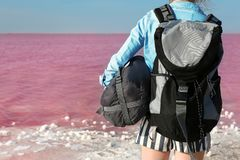 Woman with backpack and sleeping bag. On coast of pink lake stock photos