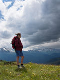 Woman with backpack standing on the field Stock Photos