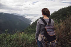 Woman with backpack standing near mountains Stock Photos