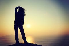 Woman with backpack standing on sunrise windy coast Stock Images