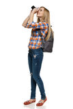 Woman with backpack taking photo Stock Photography