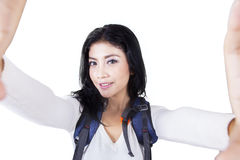 Woman with backpack taking photo in studio Stock Image