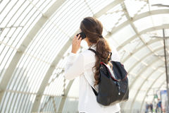 Woman with backpack talking on cellphone Stock Images