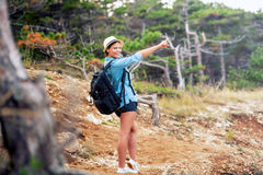 Woman with backpack trekking on mountains, walking through forest and hills. Happy woman, ready for adventure exploring the nature Royalty Free Stock Photos
