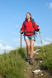 Woman with backpack and trekking poles. Smiling hiking young woman with backpack and trekking poles on the mountain trail Royalty Free Stock Images