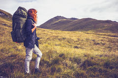 Woman with backpack trekking through the wilderness stock image