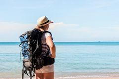 A woman with a backpack on an uninhabited island waited. For a boat Stock Images