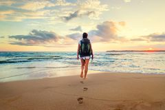 Woman with backpack walk on the ocean sand beach at sunset time Royalty Free Stock Photography