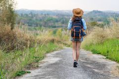 Woman with backpack walking on footpath in nature. Woman with backpack walking on footpath in the nature royalty free stock image