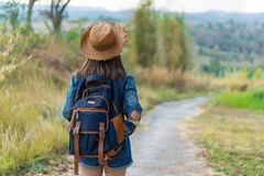 Woman with backpack walking on footpath in nature stock photos